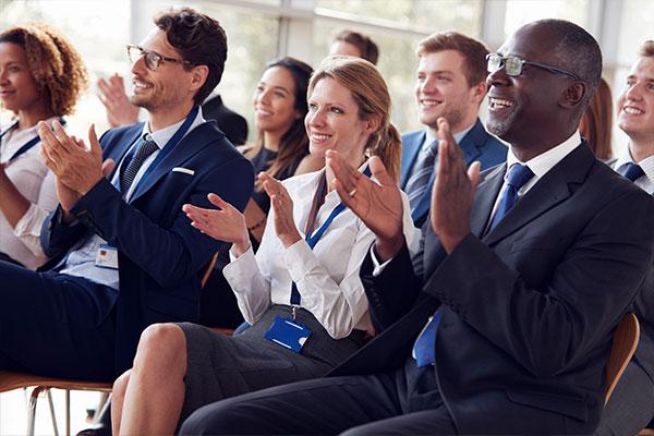 Bilden visar en samling av människor som applåderar under en konferens