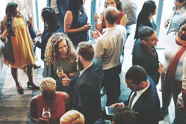 Bilden visar en samling av människor som minglar.