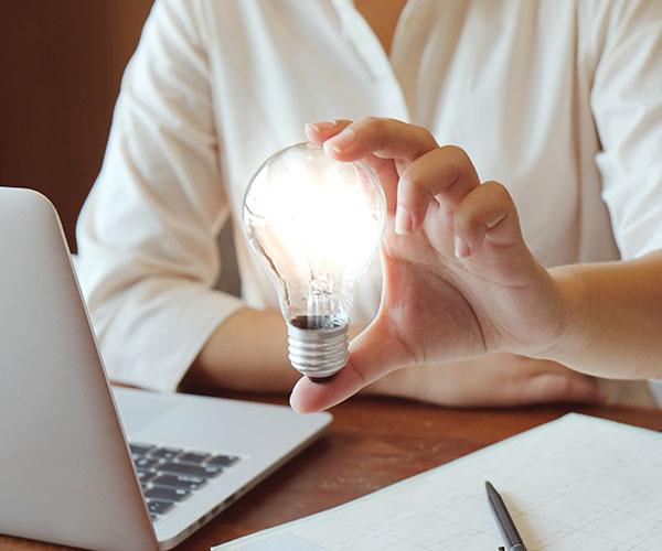 Bilden visar en kvinna framför sin bärbara dator som håller i en lysande glödlampa
