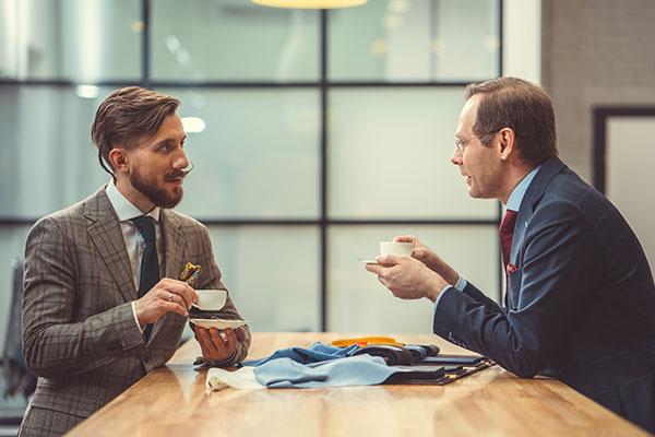 Bilden visar två kostymklädda personer som diskuterar affärer över en kopp kaffe