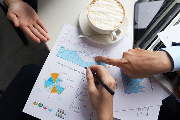 Bilden visar människor händer, på bordet finns en kopp kaffe och utskrivna papper som visar tabeller på statistik