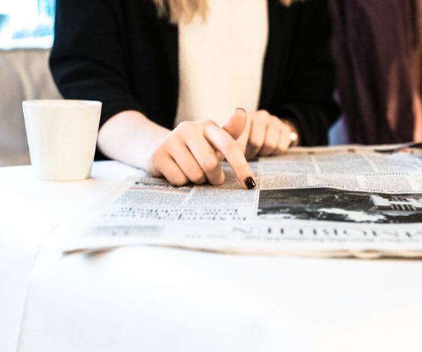 Bilden visar en kvinna som pekar på ett stycke från en tidning