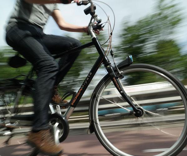 Bilden visar en människa som cyklar, bakgrunden är ur fokus