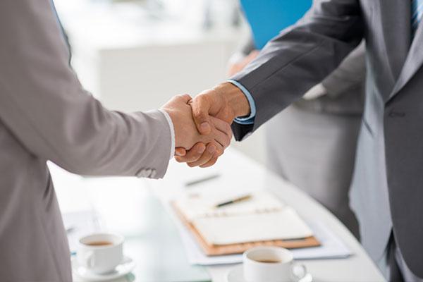 Bilden visar ett handslag mellan två affärsmänniskor