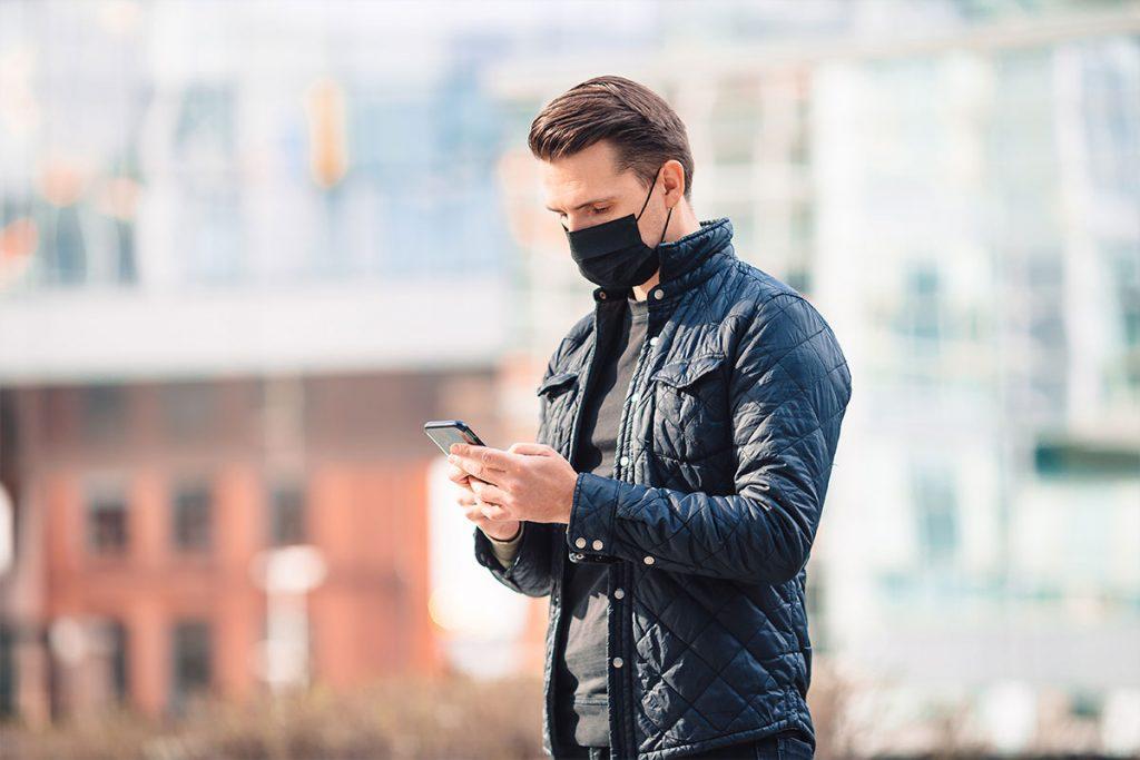 Bilden visar en man med munskydd som tittar på sin telefon under coronapandemin