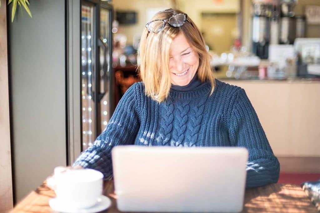 En medelålders kvinna i ett café med bärbar dator