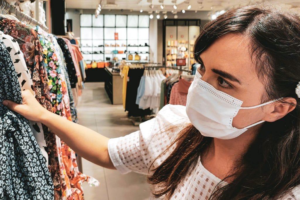 Bilden visar en ung dam som handlar kläder i en butik under coronapandemin